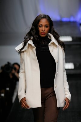 Model struts down runway in white jacket