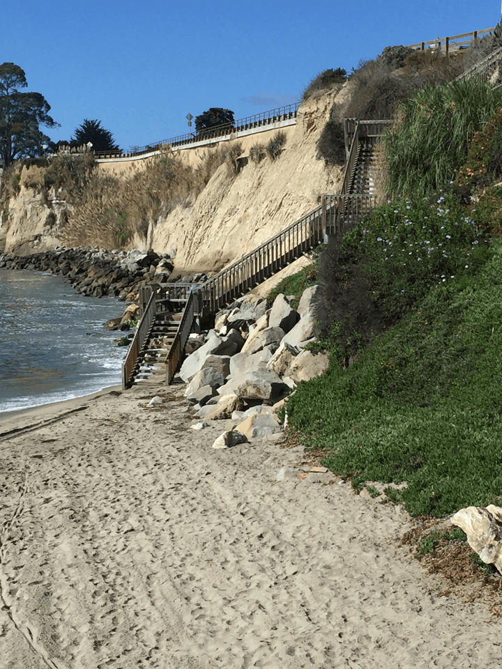 Wooden staircase ascending steep cliff on the beach