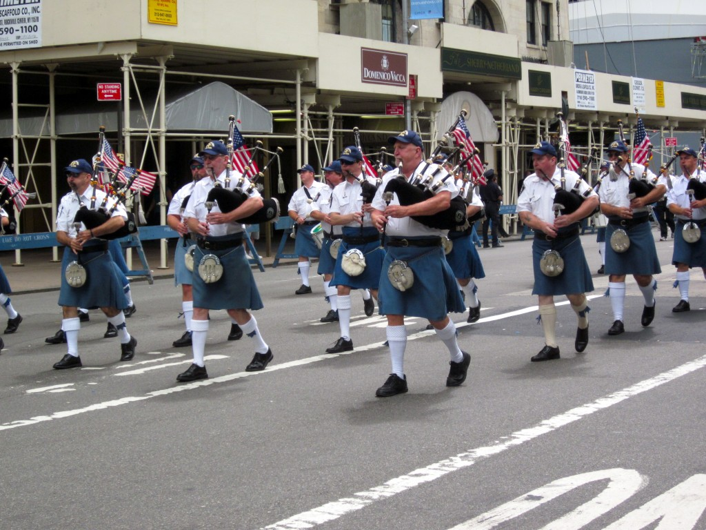 Sword and Light Pipe Band in kilts with flags
