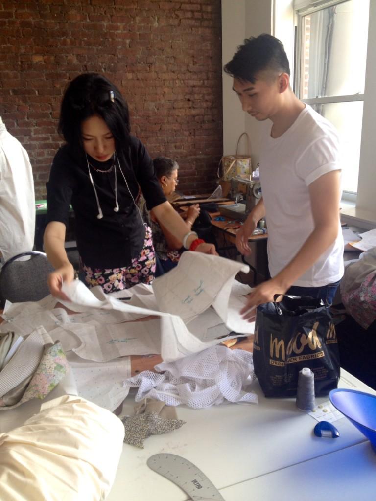 Menswear collection collaborators Jingci Wang and Max Lu, both MFA Fashion Design, consult patterns.