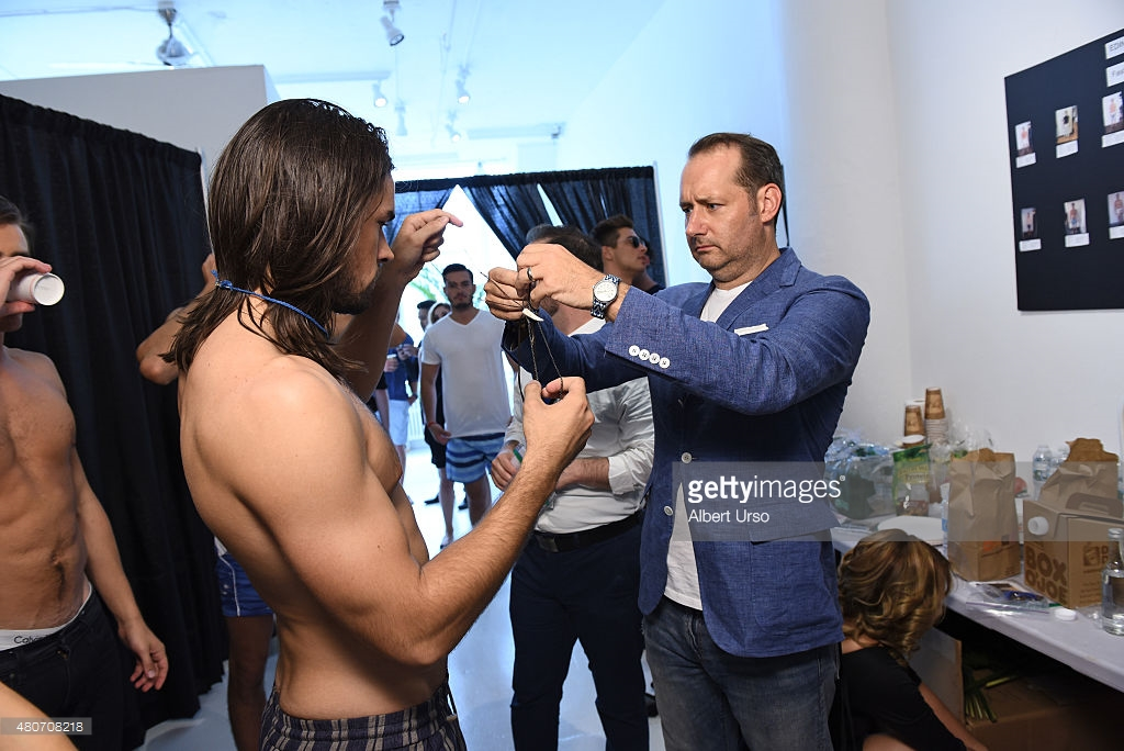 Designer Erik Nelson assists a model backstage at the Edinger Apparel presentation during New York Fashion Week; Image via Gettyimages.com