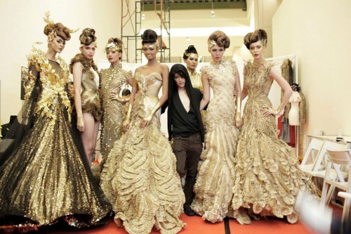 Tex Saverion surrounded by models in his designs
