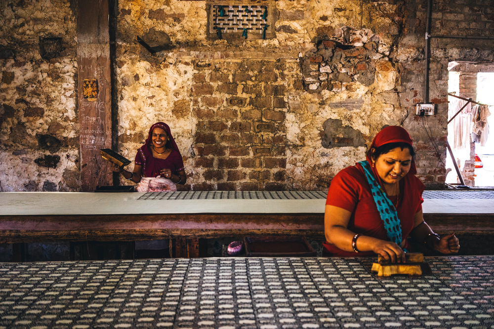 Block printing artisans share a light moment while working at a block printing unit in Bagru, outskirts of Jaipur in Rajasthan, India; Photo courtesy of Piece & Co.